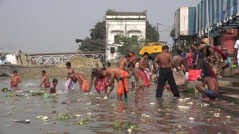 KOLKATA, INDIA - 8 DECEMBER 2014: Men take a bath at a classic bathing ghat in the Hooghly river in Kolkata.