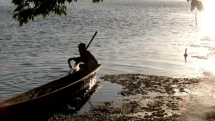 LAGUNA, PHILIPPINES - APRIL 3, 2015:  Little Boatman paddles row boat on a lake | Shutterstock HD Video #9504197