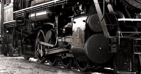Heavy industrial steam locomotive train engine wheels passing in slow motion.