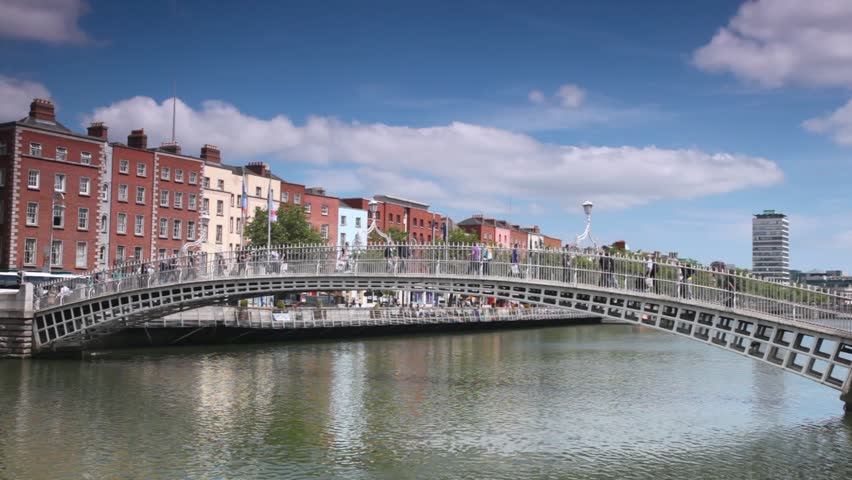 People walk on Ha'penny Bridge across River Liffey in Dublin, Ireland.