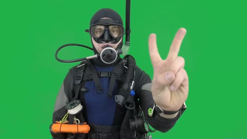 Dive instructor shows sing: COUNTING also a available on the green screen all of diving sings from course  with full dive gear (open water diver)