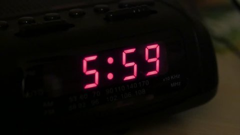 A man hits snooze on an alarm clock when it goes off at six in the morning
