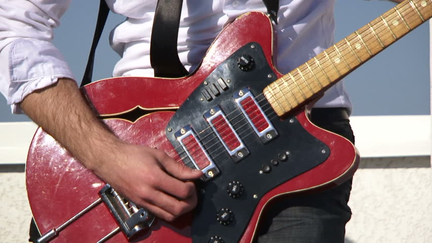 Rock musician plays guitar. Close-up.