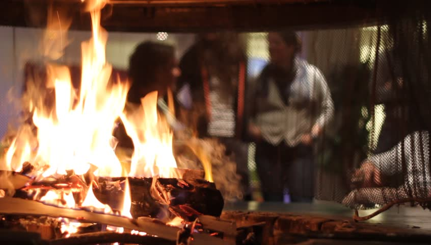FLAINE, FRANCE - MARCH 26 : Focus on the fire the fireplace with the group of unrecognizable people on the blurred background. People are talking and drinking beer together on March 26th, 2015.   Shutterstock HD Video #9564653