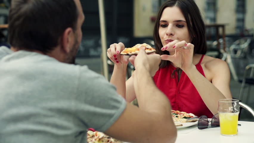 Couple eating and sharing pizza in cafe in the city