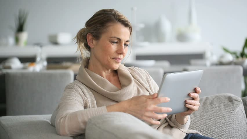 Mature woman sitting in sofa and websurfing on digital tablet