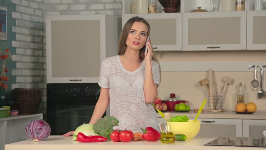 Woman Is Talking On The Phone In The Kitchen. Pretty Young Girl In ...