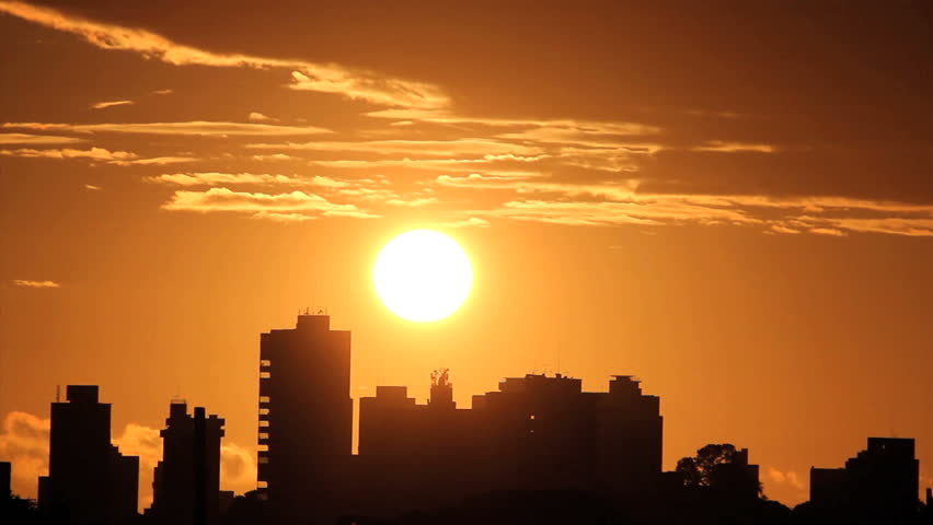Sunrise, brazilian skyline. Silhouette buildings and golden sun. Time lapse.