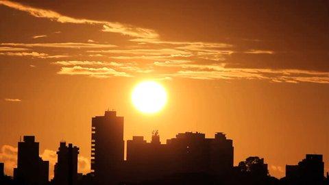 Sunrise, brazilian skyline. Silhouette buildings and golden sun. Time lapse.