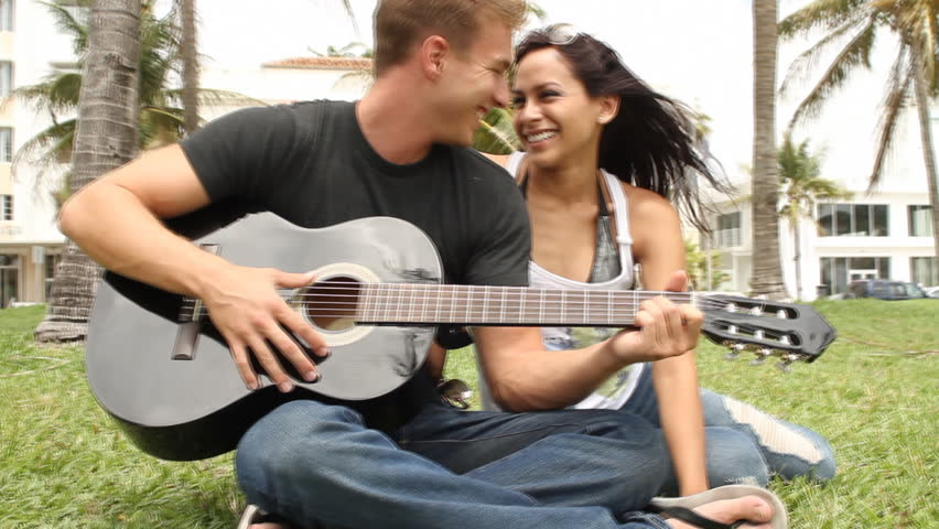 Young couple at park with guitar