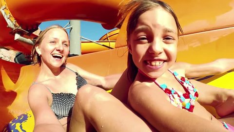 Happy woman with her daughter sliding down the waterslide in a waterpark