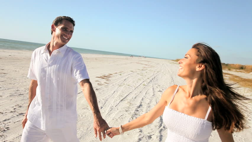 Attractive healthy couple having fun being together walking on the beach