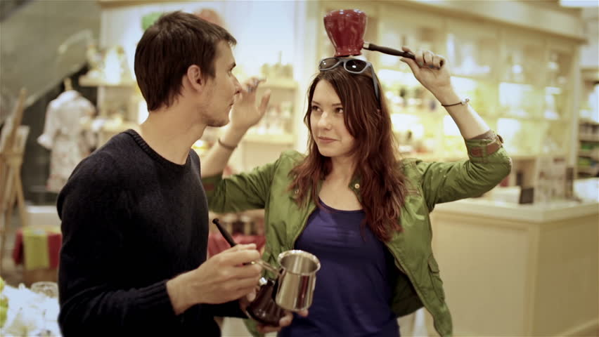 sale, consumerism and people concept shopping - happy young couple choosing cezve for Turkish coffee in mall
