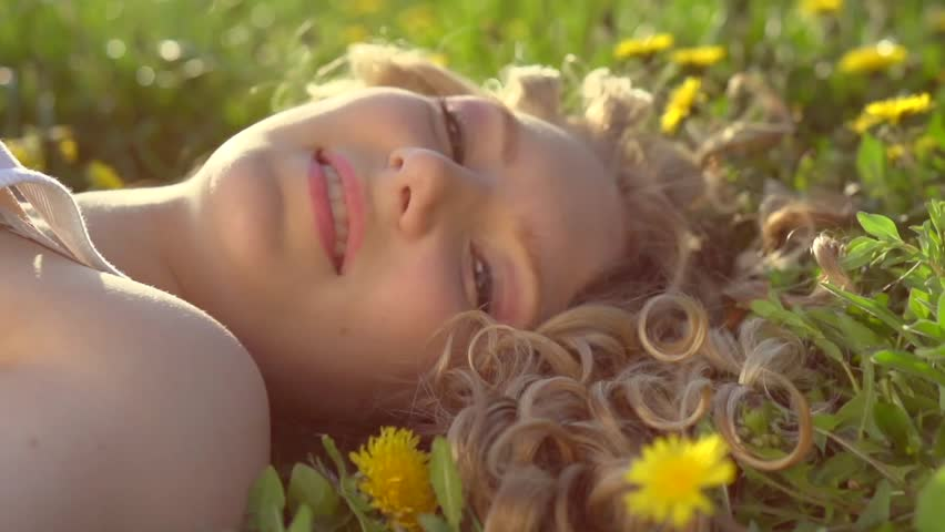 Beauty Teenage Girl lying on dandelion flowers meadow and smiling. Beautiful Spring Young Woman Outdoors Enjoying Nature. Healthy Girl in Green Grass. Allergy free. Slow motion 240 fps. 1080p #9757289