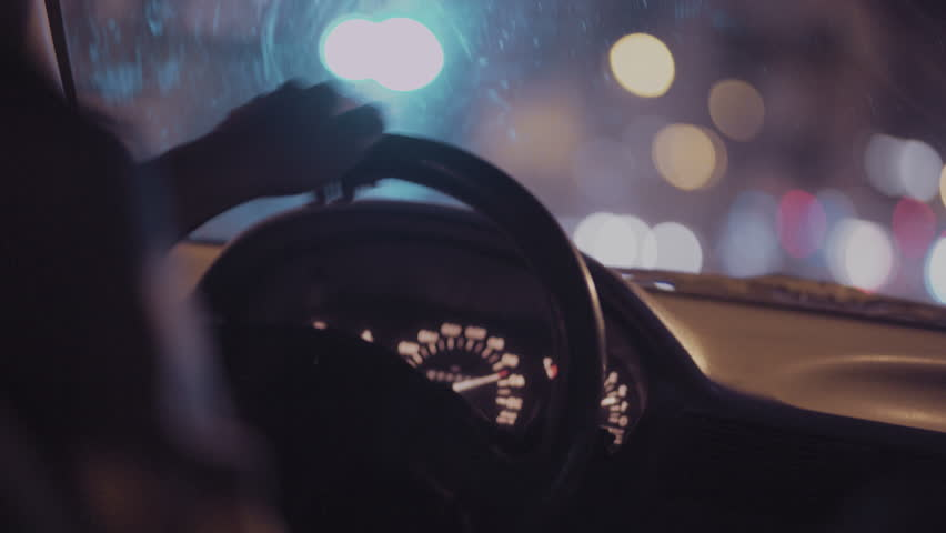 Interior view of a man driving his private taxi through the city streets at night