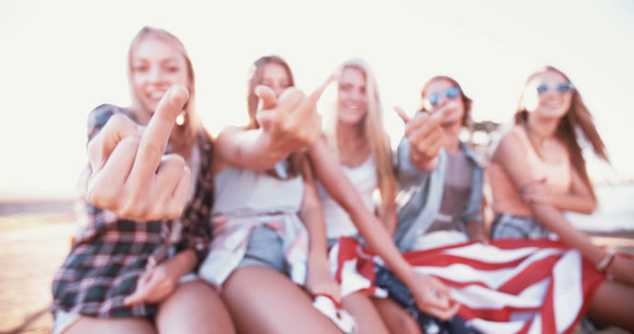 Group of rebellious teenagers holding an American flag while showing their middle fingers , Panning in Slow Motion