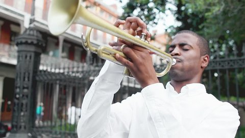 Black man plays a trumpet in the street