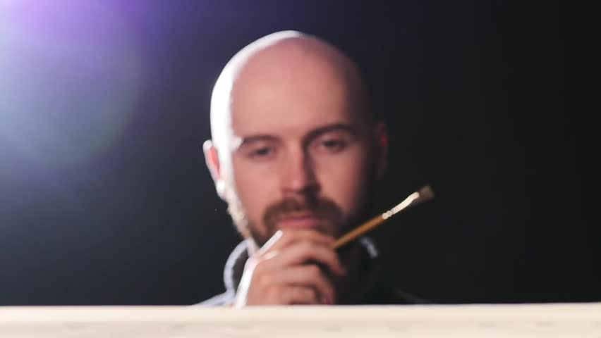 Talanted, bearded, bald artist, painter painting something and evaluates it, brush touchess his lips, doing the final touch on black background, back light, slow motion | Shutterstock HD Video #9849113