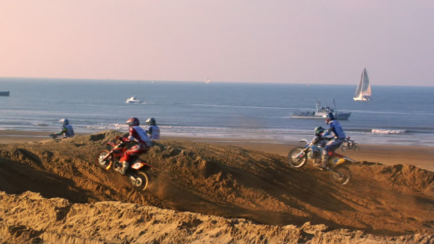 Dirt bike event on a beach with boats as spectators