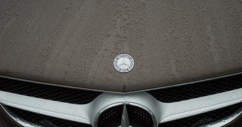 STUTTGART, GERMANY - CIRCA 2015: Mercedes Benz Sign slow-motion close-up over a sport car. Mercedes-Benz is a German manufacturer, a multinational division of the German manufacturer Daimler AG