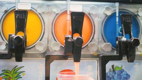 Slushy machine pouring slush ice sugar drink