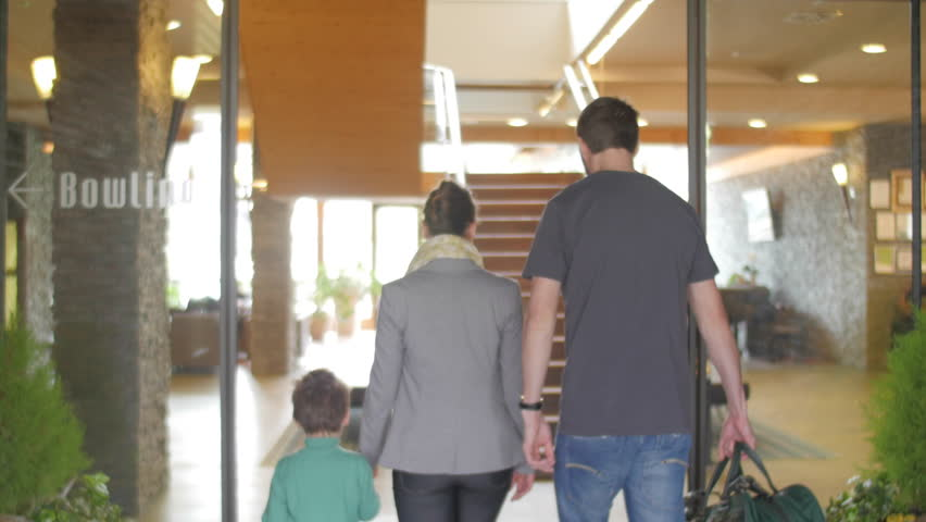 Family entering a hotel back