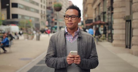 Young African Asian man in city walking texting cell phone