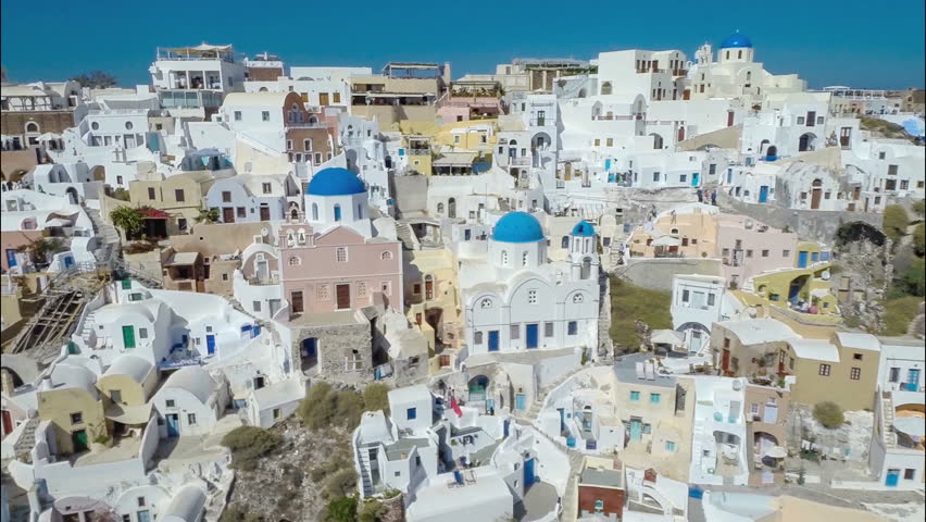 Flying above above iconic Blue Dome Churches on Santorini Island, Greece.