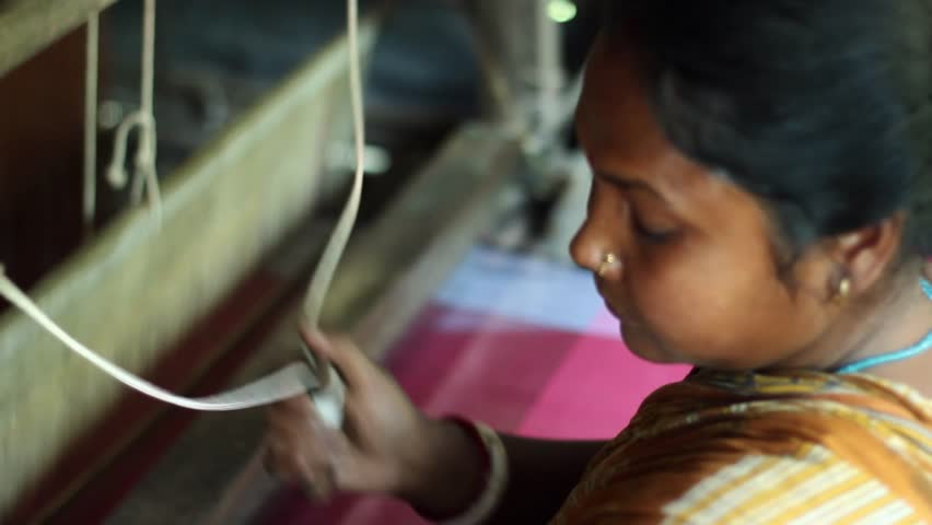 Woman weaves on loom in traditional Indian village tilt down shot. . Filmed in Bengal.