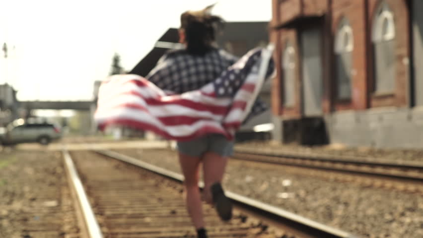 Teen Girl Runs Past Camera And Down Train Tracks, With American Flag (Slow Motion)